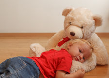 Baby and teddy bear. Baby hugging teddy bear in interior stock images