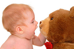 Baby and Teddy Bear. Baby talking to teddy bear, isolated on white stock photo