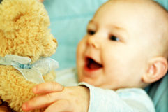 Baby and teddy bear. A cute, smiling baby playing with a teddy bear royalty free stock photography