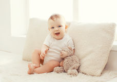 Baby with teddy bear at home in white room Stock Image
