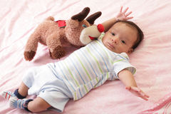 Baby with teddy bear laying on bed. Hispanic baby with teddy bear laying on bed Royalty Free Stock Photography