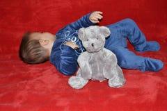 Baby with teddy bear. Lying on the sofa Stock Photography