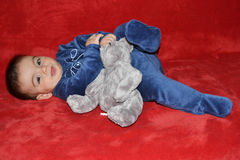 Baby with teddy bear. Lying on the sofa Stock Images