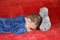 Baby with teddy bear. Lying on the sofa Royalty Free Stock Photos