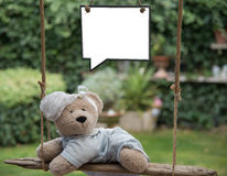 Baby teddy bear. A teddy bear baby on a swing, holding a sign where you can write a message Stock Photo