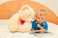 Baby and teddy with touch pad Royalty Free Stock Photography
