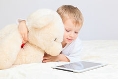 Baby and teddy bear with touch pad at home Royalty Free Stock Photo