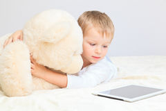 Baby and teddy bear with touch pad at home Royalty Free Stock Photos