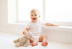 Baby with teddy bear toy sitting home in white room near wind Stock Image
