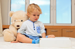 Baby and teddy with touch pad Royalty Free Stock Photos