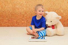 Baby and teddy with touch pad Royalty Free Stock Image