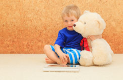 Baby and teddy with touch pad Royalty Free Stock Images