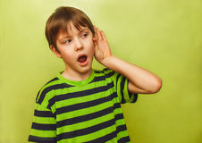 Baby teenager boy listens to put a hand his ear on Royalty Free Stock Images