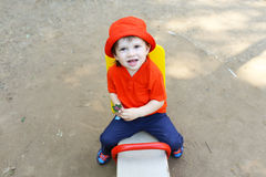 Baby on teeter-totter Stock Photography