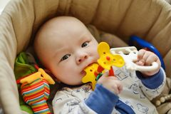 Baby with teether toy. In the crib royalty free stock photos