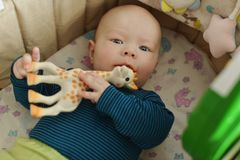 Baby with teether toy. In the crib stock photo