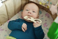 Baby with teether toy. In the crib royalty free stock image