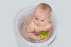 Baby Teething. Blue eyes baby girl having a bath looking up and chewing on rubber toy Royalty Free Stock Image