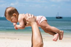 Baby is teething in dad arms. On a tropical beach. Sunny day, father throws up infant toddler, hold on hands. Child enjoyed.  royalty free stock image