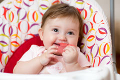 Baby with teething ring sitting in craddle Royalty Free Stock Image