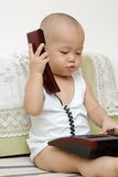 Baby with telephone. A Chinese baby with a telephone in home Royalty Free Stock Images