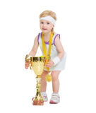 Baby in tennis clothes holding medal and goblet Stock Images