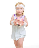 Baby in tennis clothes holding piggy bank Royalty Free Stock Photo