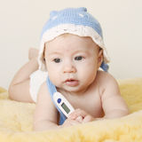 Baby with thermometer. Cute thoughtful baby with thermometer Stock Images