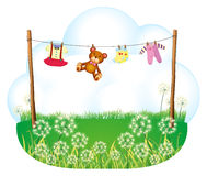 Baby things hanging above the weeds Stock Photo