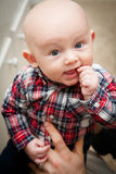 Baby With Thumb in Mouth. Happy baby with big blue eyes wide open with a finger in his mouth looking upward wearing a plaid shirt Stock Photo