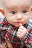 Baby With Thumb Near Mouth. Happy baby with big blue eyes wide open with a finger near his mouth Royalty Free Stock Images