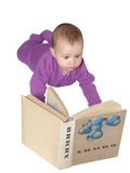The baby thumbs through the textbook of chemistry. On the book it is written in Russian `Chemistry Stock Photo