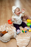 Baby on tiger mat. Cute baby girl sits on a tiger mat at home royalty free stock photos