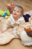 Baby on tiger mat. Cute baby girl lies on a tiger mat at home royalty free stock photo
