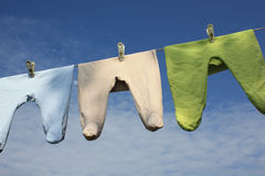 Baby times. Baby crawlers hanging on the clothesline against the sky Stock Images