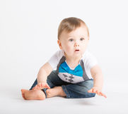 Baby About to Crawl. A cute 1 year old sits in a white studio setting. The boy looks like he is about to start crawling. He is dressed in Tshirt, jeans Stock Photos
