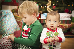 Baby and Toddler Boy Enjoying Christmas Morning Near The Tree Stock Photo