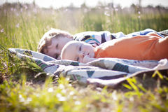 Baby and toddler brothers lying on quilt Royalty Free Stock Images