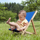 Baby on deckchair in garden. Baby or a toddler child playing on a sunbed or a deck chair in a garden Royalty Free Stock Image