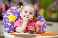 Baby toddler eating in chair Stock Photography