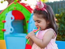 Baby toddler girl eating a large colorful lollipop dressed in pink dress as princess or queen. With crown, playing outdoor in garden with playhouse stock photography