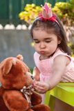 Baby toddler girl, mouth full of candies playing in a tea party feeds best friend Teddy Bear with candy Stock Image