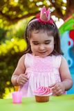 Baby toddler girl in outdoor party at garden, happy and smiling at cupcake with sweet tooth expression. Pink dress and queen or princess crown Royalty Free Stock Images