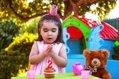 Baby toddler girl in outdoor second birthday party clapping hands at cake with Teddy Bear as best friend. Playhouse and tea set. Pink dress and crown Stock Photos