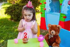 Baby toddler girl in outdoor second birthday party clapping hands at cake with Teddy Bear as best friend. Playhouse and tea set. Pink dress and crown Stock Photography