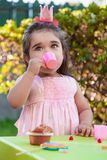 Baby toddler girl playing in outdoor tea party drinking from cup with lollipop, muffin and gummies on table. Pink dress and queen or princess crown Stock Images