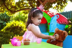 Baby toddler girl playing in outdoor tea party feeding her best friend Teddy Bear with candy Stock Images