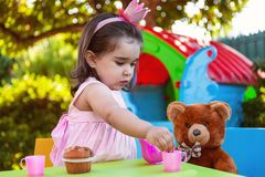 Baby toddler girl playing in outdoor tea party serving her best friend Teddy Bear with candy gummy royalty free stock image