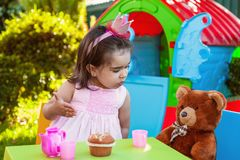 Baby toddler girl playing in outdoor tea party talking, chatting or sharing to her best friend Teddy Bear Stock Photos