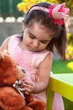 Baby toddler girl, playing in a tea party feeds best friend bff Teddy Bear with candy gummy stock photography